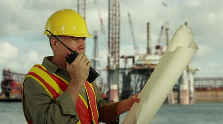 mořský : Man in hardhat and safety vest holding rolled up schematics or plans and talking on two-way radio with drilling platforms in background. Dostupné videozáznamy
