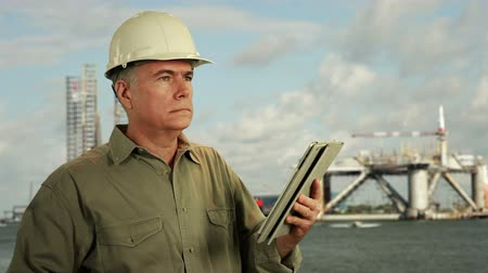 mérnök : Man in hardhat with drilling platforms in background uses electronic tablet.