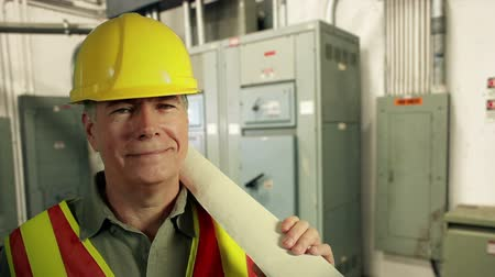 disjuntor : Electrical panels and conduit is the backdrop for a man in a hardhat holding rolled up circuit drawings.