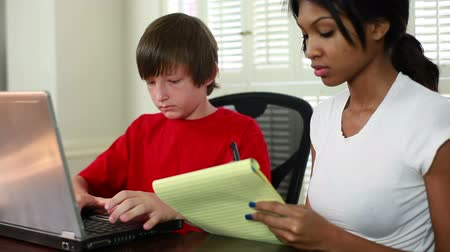 ödev : Boy using laptop as his pretty African American tutor looks on. Focus starts on tutor then moves to student.