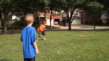hurl : Two young boys catching and returning a baseball being thrown to them by their father.