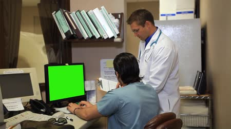 egészségügy és az orvostudomány : Two doctors reviewing something on a computer screen stop, turn, and smile for the camera. Stock mozgókép