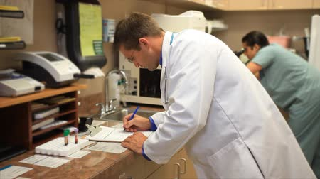 szpital : A doctor and a nurse or technician working in a clinics small laboratory.