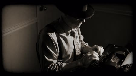 maszyna do pisania : The camera pans from a stark shadow of a person to a man wearing a fedora and typing on a vintage 40?s typewriter. Film Noir, old film effect