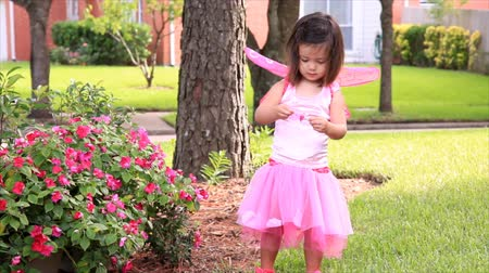 восхищенный : A darling little girl dressed in a pink fairy costume, playing with flowers in a garden. Стоковые видеозаписи