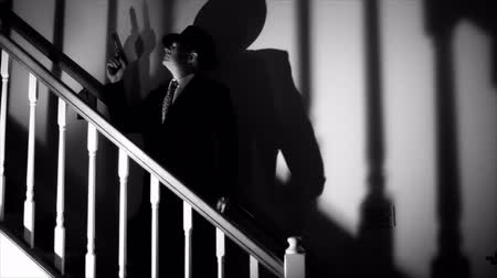 przestępca : Deep shadows surround a man with a gun slowly walking up a staircase. Wideo