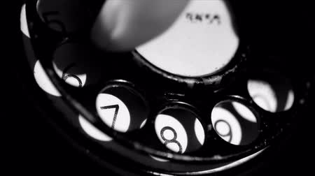 korszak : A closeup of someone dialing on an old rotary style telephone