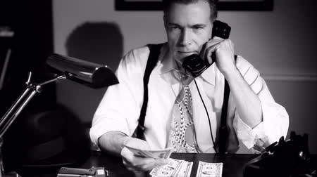 pieniądze : A man sitting counting money with a pistol placed carefully within reach answers the telephone. Film Noir, Vintage 40?s look
