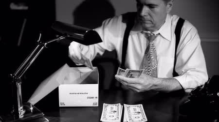 hoard : A man sitting counting money and putting it into a shoe box for safe keeping. Film Noir, Vintage 40?s look