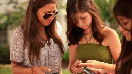 chatting : Three pretty teenage girls have fun using their cell phones to send text messages.