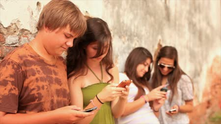 conversando : A group of teenagers hanging out by an old brick wall, using cell phones to send text messages and talking to each other.