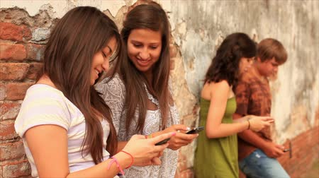 nastolatki : A group of teenagers with cell phones, hanging out by an old brick wall.