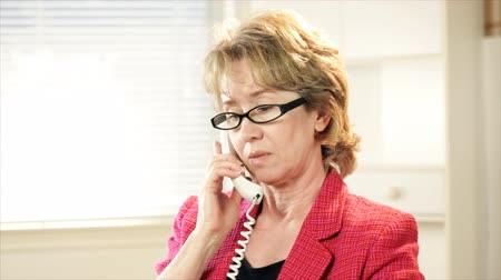 asistan : A mature businesswoman in her office conducting business over a desk phone.