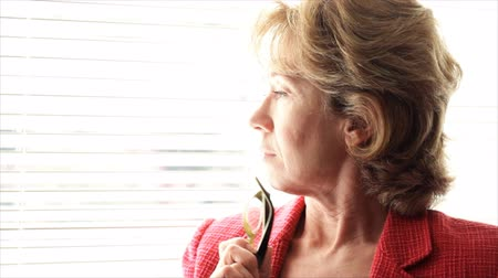 rolety : A mature woman deep in thought, looking at something from a sunlit window. Wideo