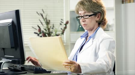 deneyimli : A mature woman in a white lab coat working at her computer.