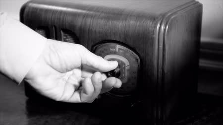 régi : A man?s hand turns the dial on an old vintage 1940?s radio until he finds the music he is looking for, stops and starts tapping his finger. Film Noir Stock mozgókép
