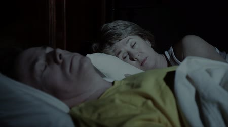 беспокоюсь : A sleepless woman lies wide awake in bed while her husband is sleeping soundly next to her.