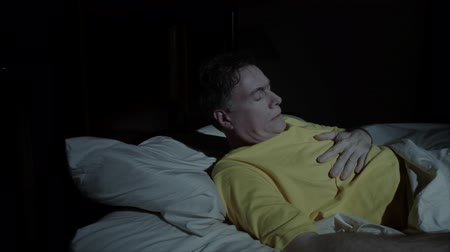 dyspepsia : A mature man is awakened by stomach pain, heartburn, or indigestion. Stock Footage