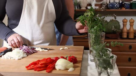 culinária : A culinary chef stops chopping galic and takes fresh herbs from a glass that a woman has brought her.