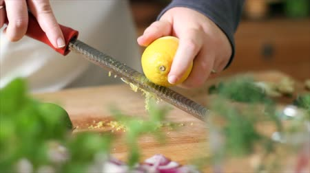 citrón : A chef using a special grater or zesting tool to produce citrus zest from the rind of a fresh lemon. Dostupné videozáznamy