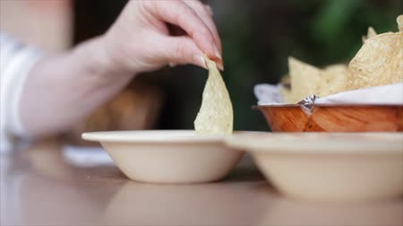 dips : Close up of a woman?s hand holding a crisp tortilla chip and dipping into some salsa verde.