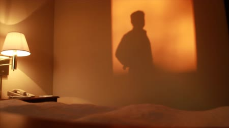 vago : Warm late afternoon sunlight pouring into a hotel room casts a shadow on the wall of a man pacing back and forth.