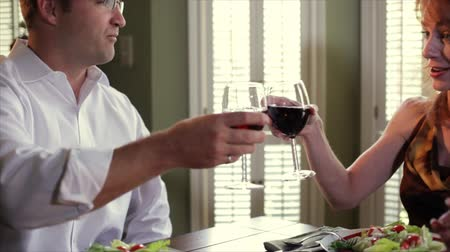 salata : A happy man and a smiling redheaded woman drinking red wine toast each other while engaging in pleasant conversation. Camera tilts and pans. Stok Video