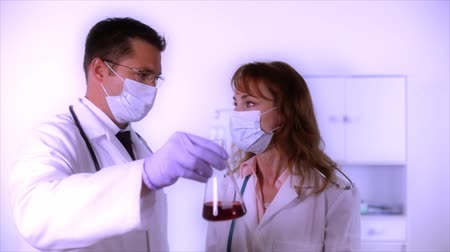 espécime : Two doctors consult while examining a red specimen they have in a glass laboratory flask. Tinted, softened, and glow added for affect. Vídeos