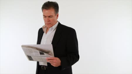 gazete : A businessman paces back and forth as he reads a newspaper and drinks from a coffee cup. White backdrop, copy space, isolated on white, Newspaper is fake, create specifically for the video.