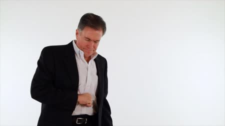 stres : A man dressed in a suit suffering from indigestion or heartburn. White backdrop, copy space, isolated on white