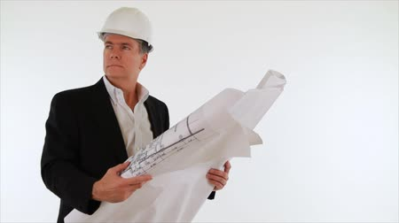 compares : A man who appears to be an architect or engineer with a set of plans in his hands compares what he is seeing off camera to what he sees on paper. White backdrop, isolated on white. Stock Footage