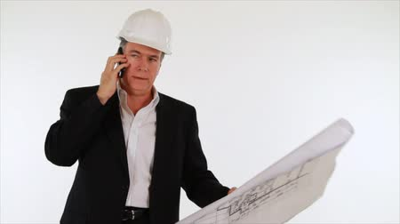 stavitel : A man who appears to be an architect or engineer with a set of plans in his hand engages in conversation using his cell phone. White backdrop, isolated on white.