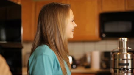 braces on teeth : A pretty girl standing in a kitchen smiles at someone off camera as her grandmother enters the room and the camera pans over to another girl. Stock Footage