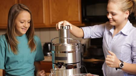 cimborák : Two adolescent girls standing in a kitchen cut and add fruits and vegetables to a juicer to make a nutritious vitamin packed drink. Stock mozgókép