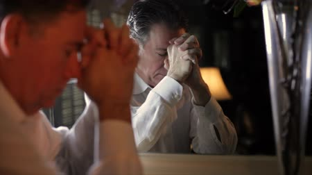 odrážející : An anxious man standing in front of a mirror folds his hands as if praying, then turns and stares with troubled eyes at his reflection.