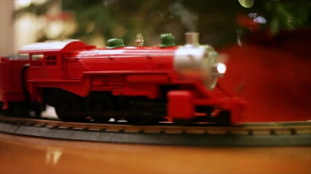 boŻe narodzenie : A bright colored toy electric train chugs along a track placed around the base of a decorated Christmas tree. Wideo
