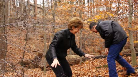 rywalizacja : A mature couple playfully throwing autumn leaves at each other during a walk through the woods. Wideo
