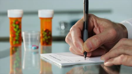 indústria : A close up of a male physicians hand writing out a prescription with out of focus pharmaceuticals pill bottles in the background.