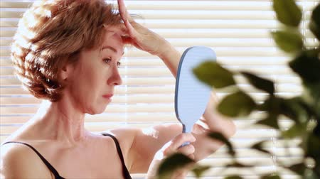amadurecer : A mature woman looking in a mirror becomes dissatisfied with her reflection and begins to examine her aging skin. Camera is on a tripod but pans and tilts ever so slightly following the womans movements.