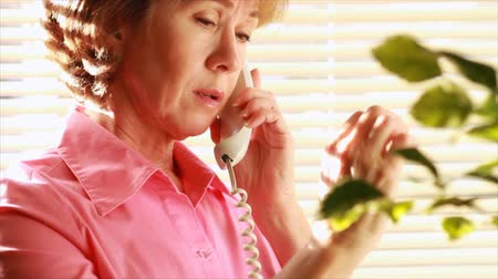 arthritis : An older woman concerned about the pain she is experiencing in her fingers due to arthritis talks on the phone someone about her problem. Stock Footage