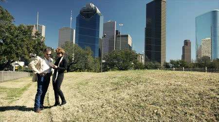 решить : A man and a woman talking in a downtown green space or park with metropolitan Houston looming in the background decide to take a walk towards the city.