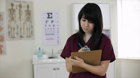 yazarak : A pretty young nurse in a clinic stops writing on her clipboard and smiles at the camera. Dolly Shot, Shallow depth of field