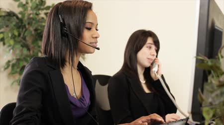 serwis : A lovely African American girl and a co-worker working the helpdesk using a headset and a regular desk phone. Shallow depth of field.