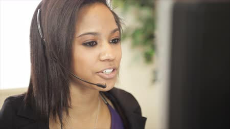 képviselő : A lovely African American girl wearing a headset works at her computer and talks to someone calling in to the helpdesk.