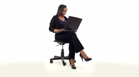 yazarak : A young attractive African American woman sitting in a swivel chair typing something on her laptop. Taken on a white backdrop. Stok Video
