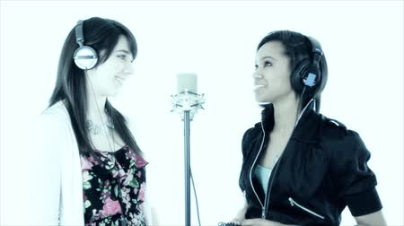 škádlení : Two vivacious pretty girls wearing headphones standing in front of a microphone engaged in lively banter as if for a radio show. Taken against a white backdrop. Tinted blue for effect. Dostupné videozáznamy