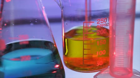 chemistry : A crystallized substance is stirred into a chemistry beaker filled with a yellow liquid while a flask and a graduated cylinder remain in soft focus in the foreground. Stock Footage