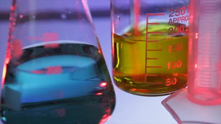 chemistry : A yellow liquid being stirred in a chemistry beaker with a graduated cylinder and flask containing green liquid in the foreground. Stock Footage