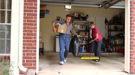 szervez : Spring cleaning time for this couple working to tidy up their garage. Stock mozgókép
