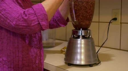 concoction : A woman adding a ripe banana to a fruit smoothie she is making in a blender.
